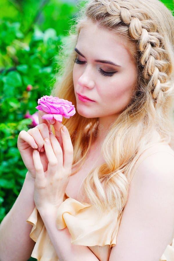 拿着开花的玫瑰色花的妇女 免版税图库摄影