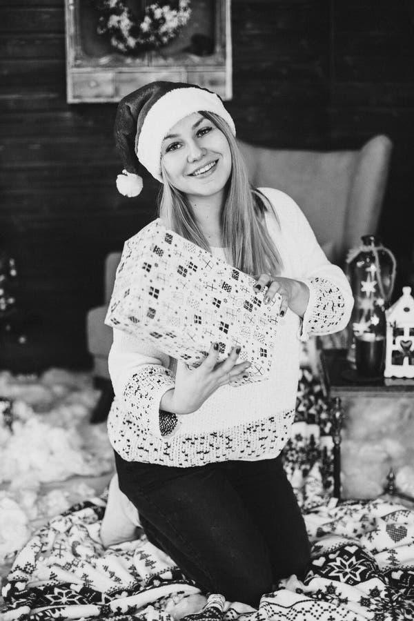 拿着当前箱子的圣诞老人帽子的愉快的妇女 免版税库存照片