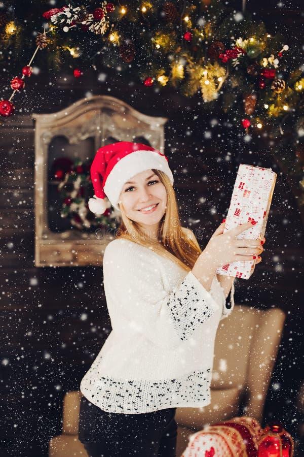 拿着当前箱子的圣诞老人帽子的愉快的妇女 免版税库存图片