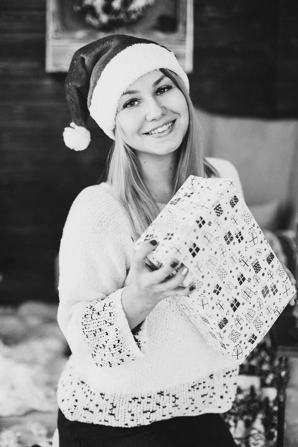 拿着当前箱子的圣诞老人帽子的愉快的妇女 免版税图库摄影