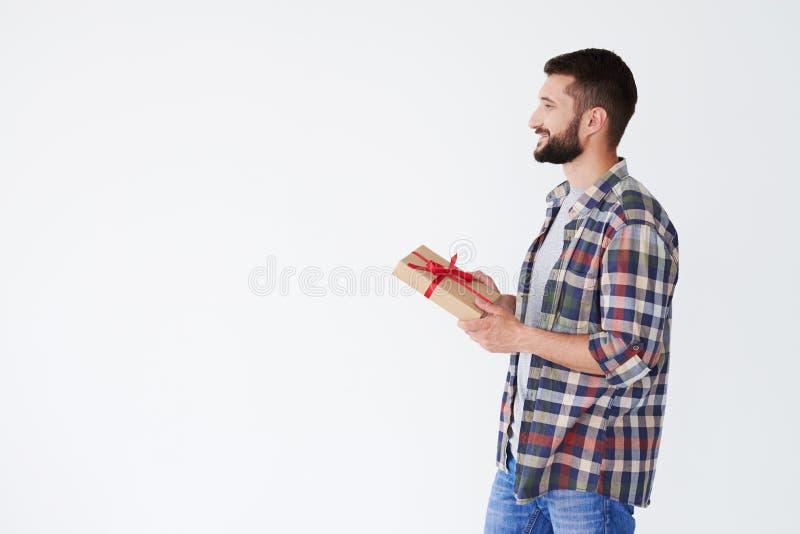 拿着当前箱子的愉快的有胡子的人侧视图  库存图片