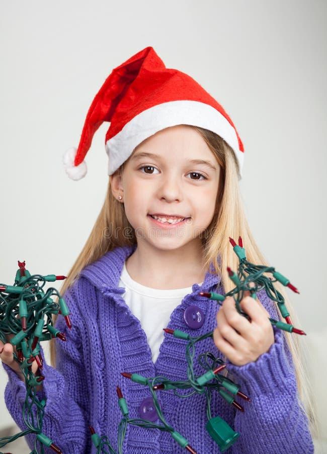 拿着彩色小灯的圣诞老人帽子的女孩 图库摄影