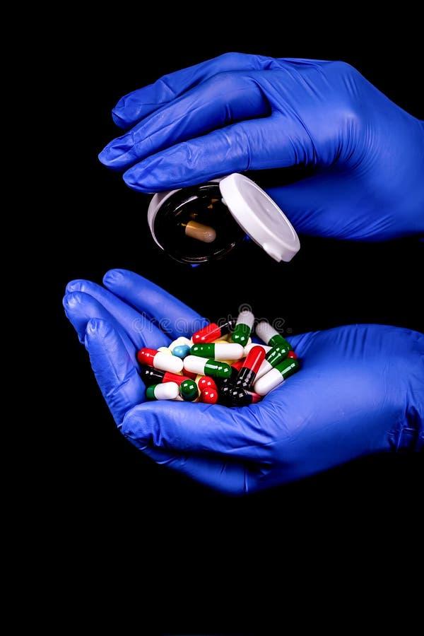 拿着很多不同的色的胶囊和药片的女性手 免版税库存照片