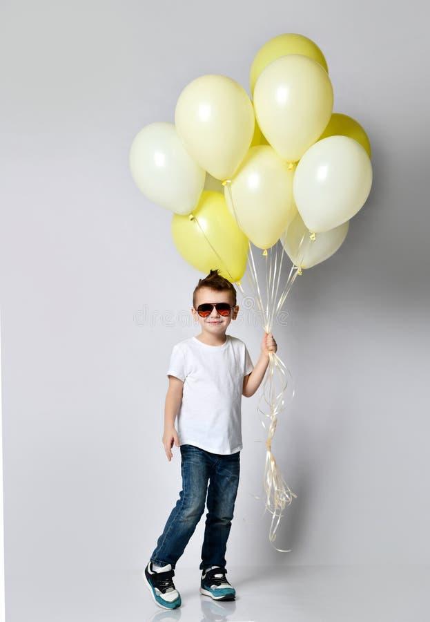 拿着很多气球的逗人喜爱的孩子 免版税库存照片