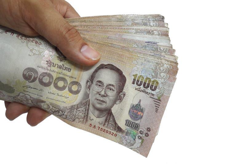 拿着很多1,000泰铢泰国钞票的手被隔绝在与裁减路线的白色背景 库存照片
