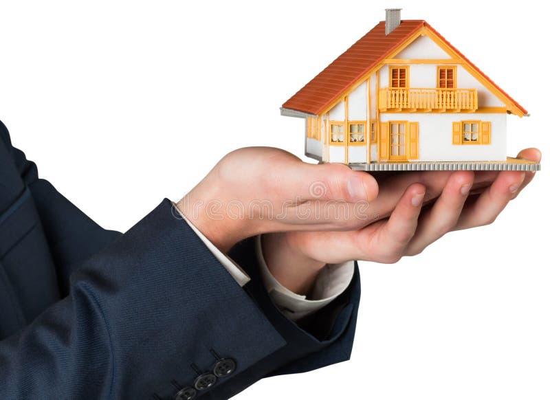 拿着微型房子模型的商人 皇族释放例证