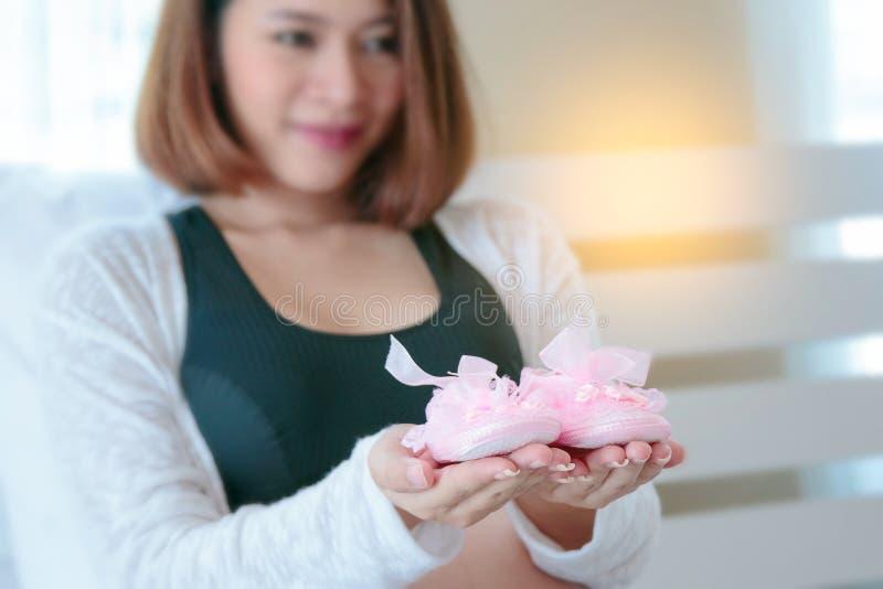 拿着微小的鞋子的愉快的孕妇 免版税图库摄影