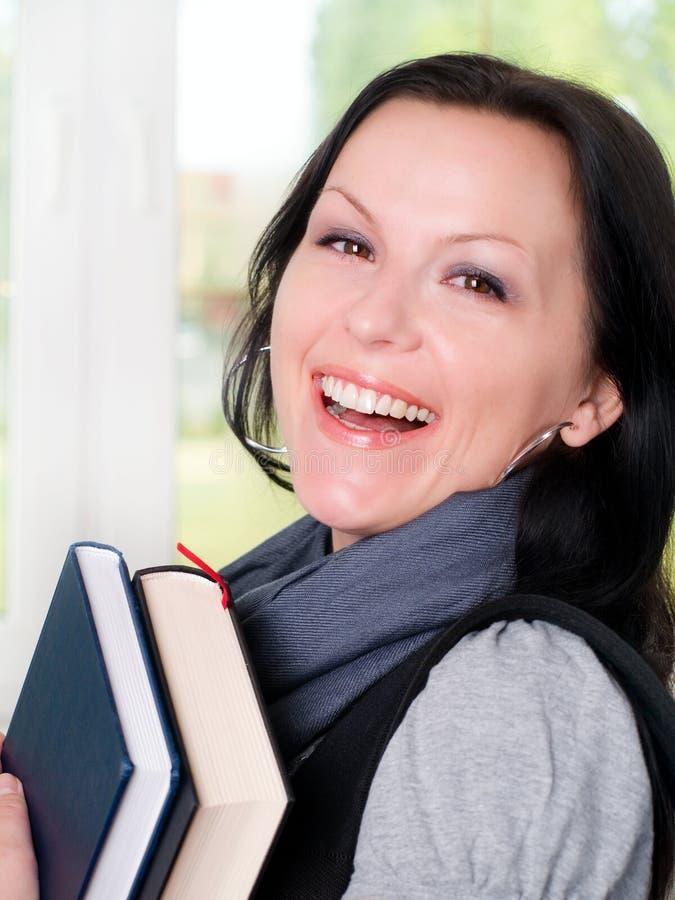 拿着微笑的学员妇女的书 免版税库存照片