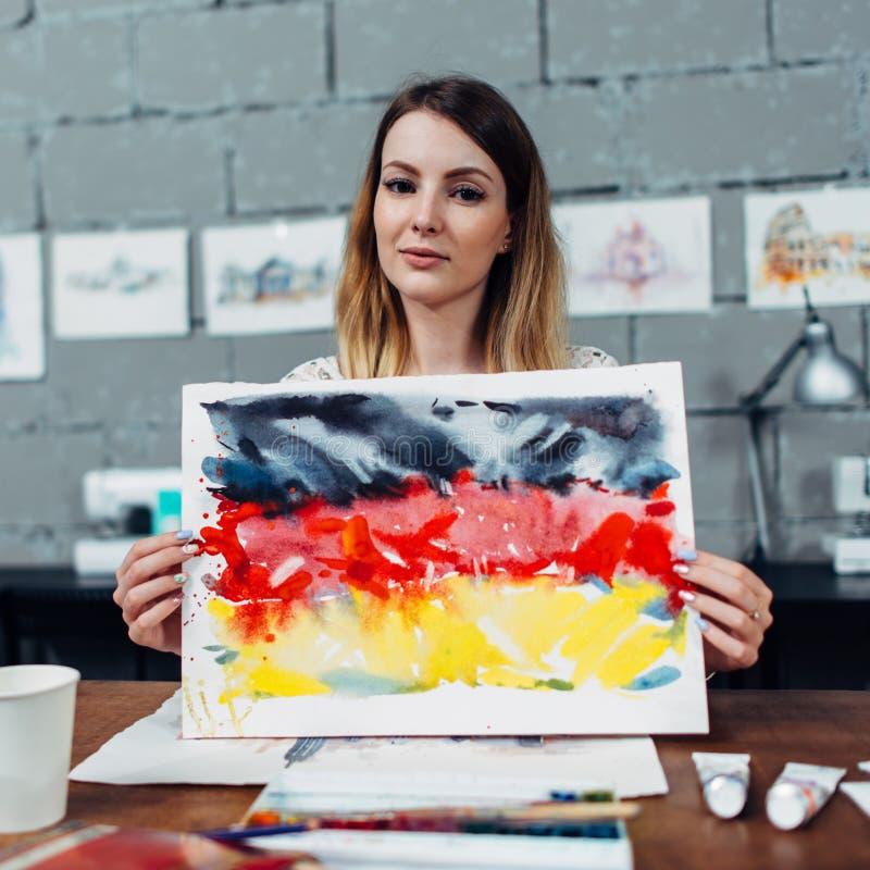 拿着德国旗子的绘画创造性的年轻女性设计师显示坐在时髦的车间的一个新的印刷品想法 免版税库存照片