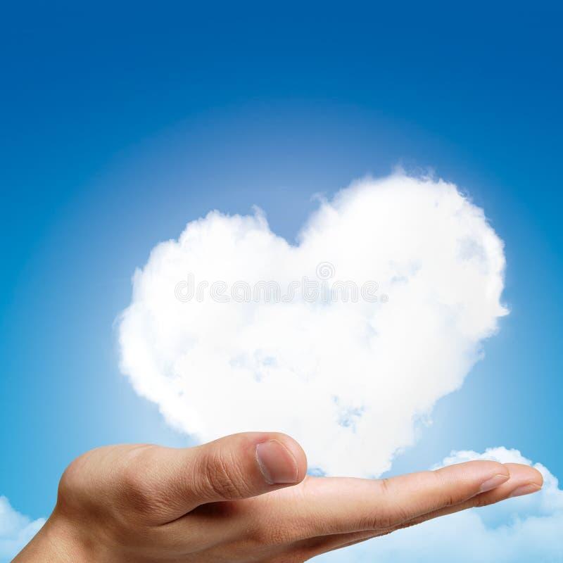 拿着心形的云彩和蓝天的手 免版税库存照片