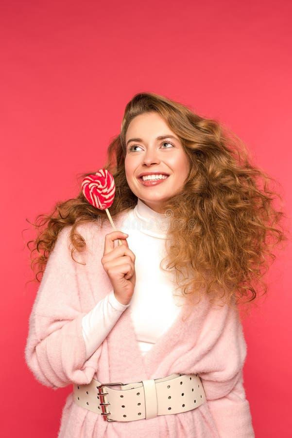 拿着心形的棒棒糖的微笑的女孩 免版税库存图片