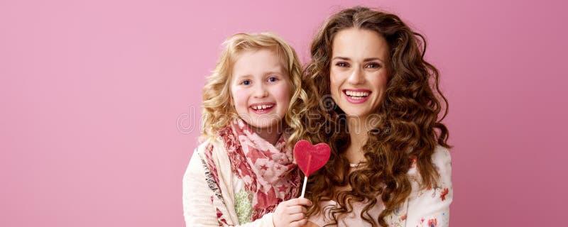 拿着心形的棒棒糖的微笑的时髦的母亲和孩子 免版税库存照片