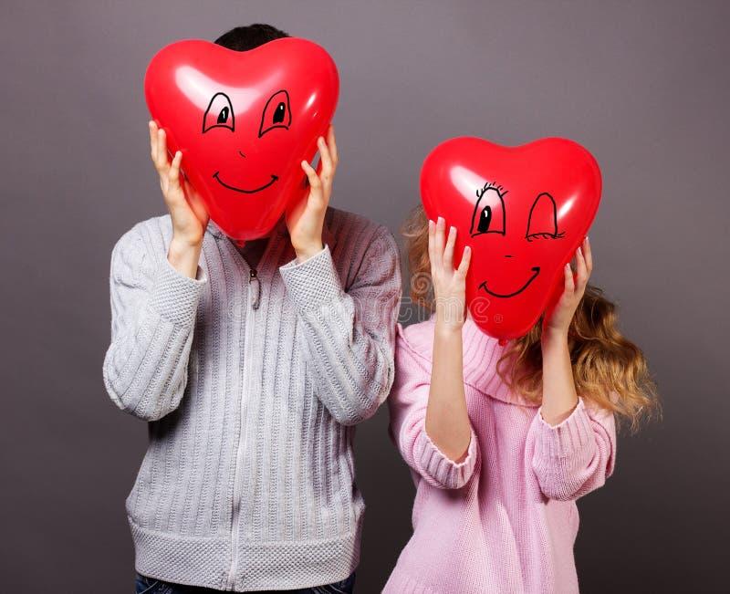 男孩和女孩拿着气球红色心脏的白色背景的.