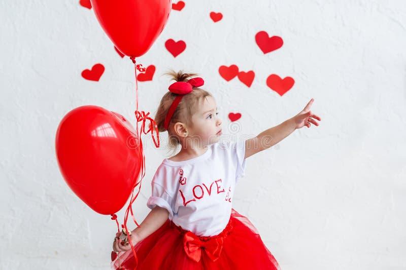 拿着心形的气球的俏丽的可爱宝贝女孩在圣徒情人节 库存照片