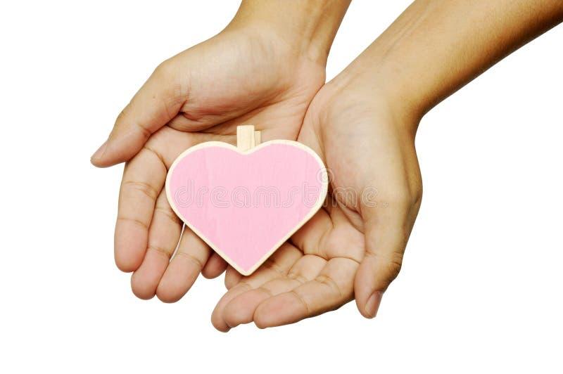 拿着心脏形状木标志的人的手 免版税库存图片