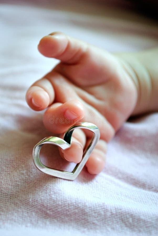 拿着心脏的婴孩的手 库存图片