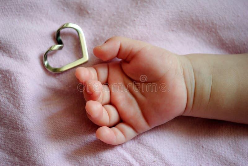 拿着心脏的婴孩的手 免版税库存照片