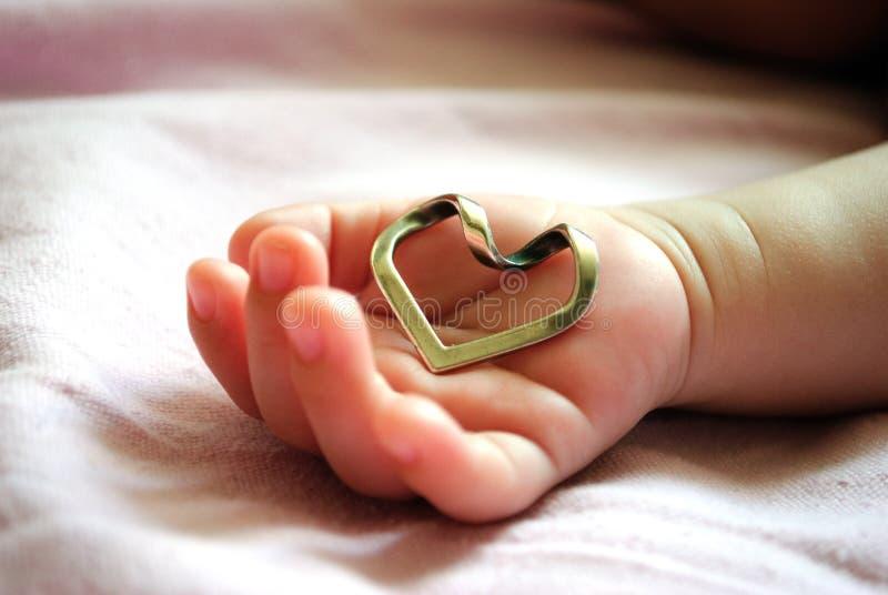 拿着心脏的婴孩的手 免版税库存图片