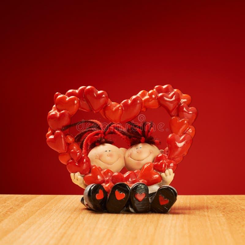 拿着心脏的陶瓷男孩和女孩形象塑造 免版税库存图片