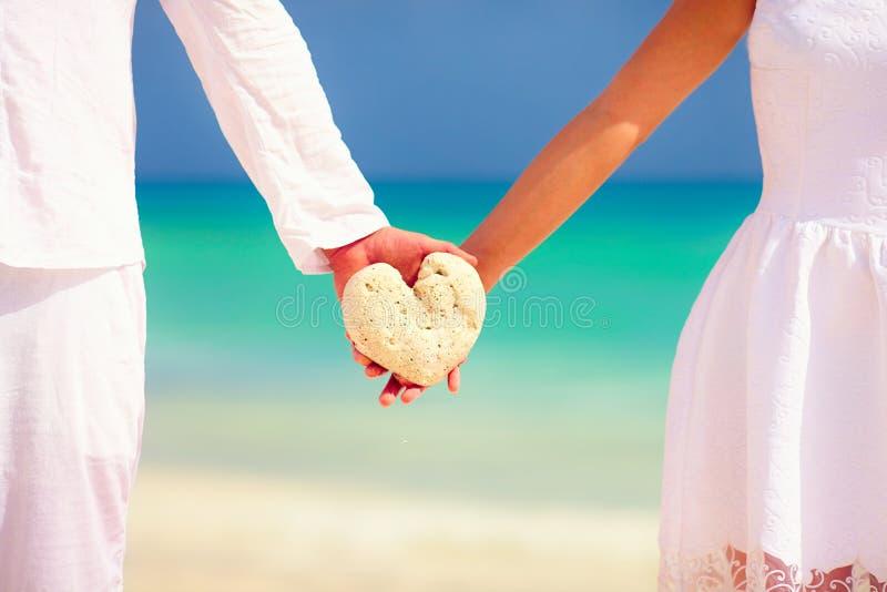 拿着心脏的年轻夫妇塑造在热带海滩的石头 库存图片