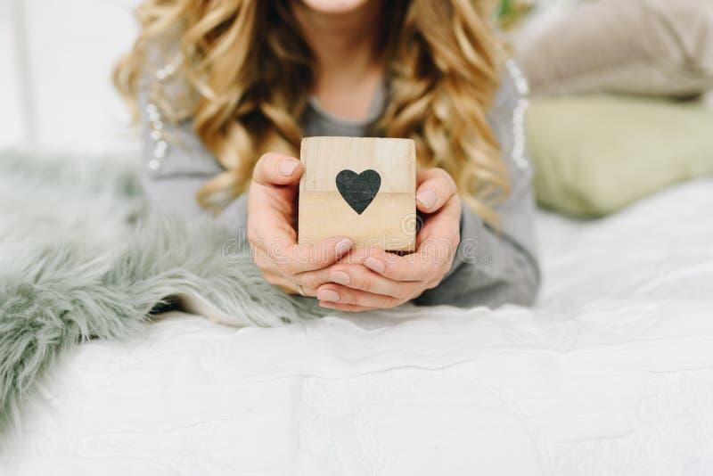 拿着心脏,爱的标志的美丽的年轻白种人欧洲妇女 免版税库存照片
