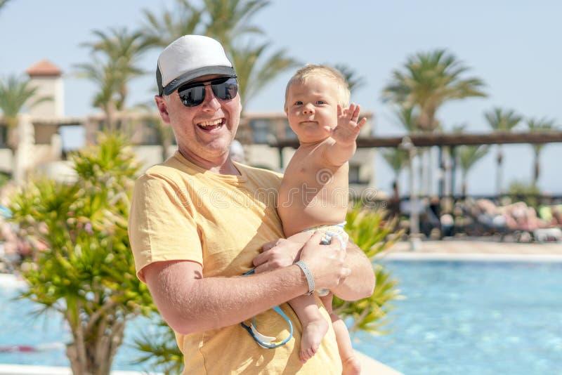 拿着快乐的儿子的愉快的父亲在热带假期时 免版税库存照片
