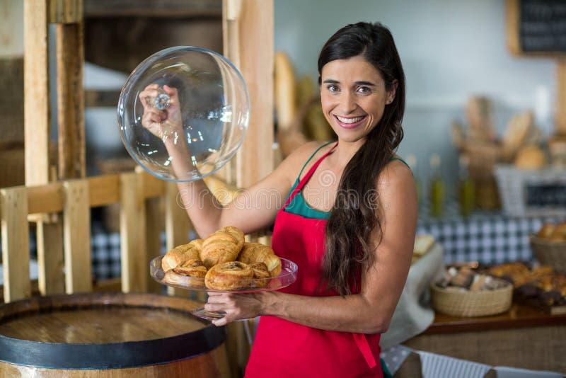 拿着快餐的盘子微笑的女职工画象在柜台 库存图片