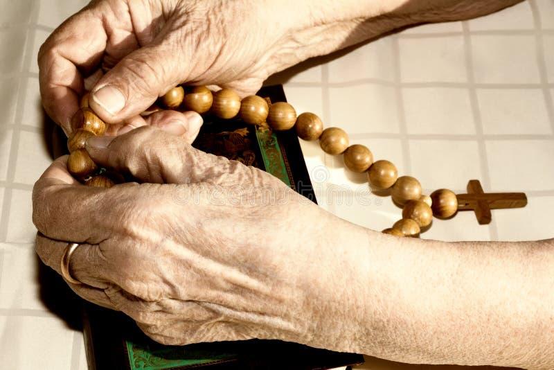 拿着念珠的老妇人的手 库存照片