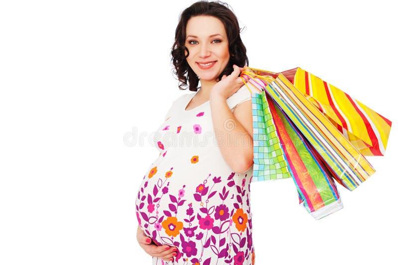 拿着怀孕的购物妇女的袋子 免版税库存图片