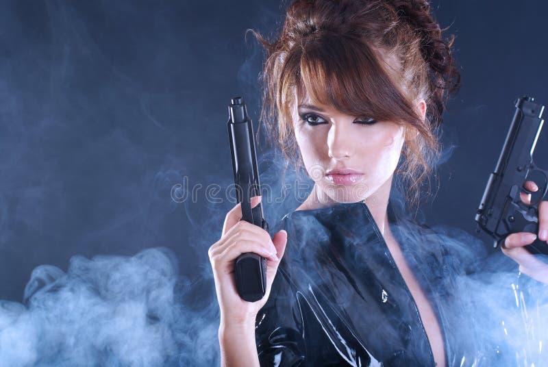 拿着性感的烟妇女的枪 免版税库存图片