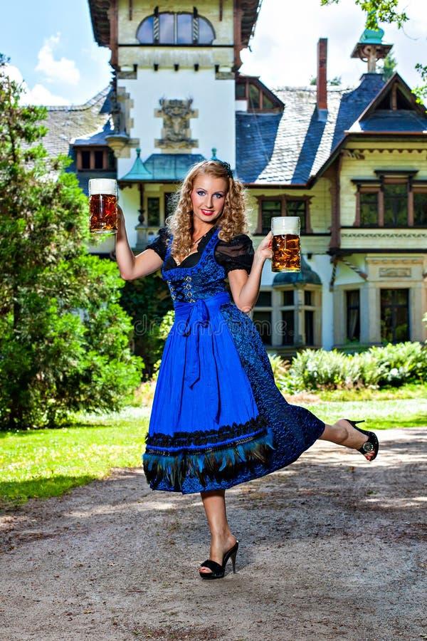 拿着慕尼黑啤酒节啤酒的微笑的妇女 免版税图库摄影