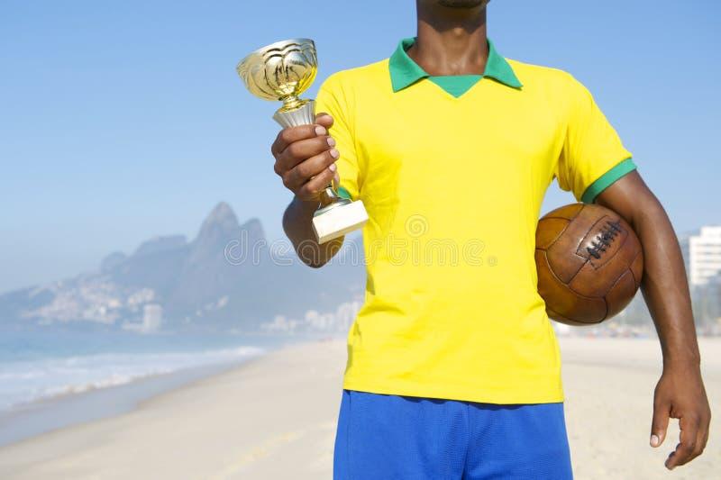 拿着战利品和足球的冠军巴西足球运动员 免版税库存照片