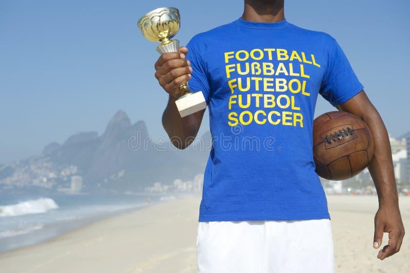 拿着战利品和足球的冠军巴西足球运动员 图库摄影