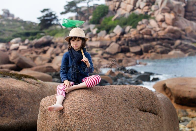 拿着户外活动的乏味孩子鱼网在度假 免版税库存照片
