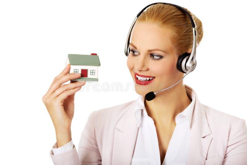 拿着房子模型的耳机的年轻女商人 库存图片