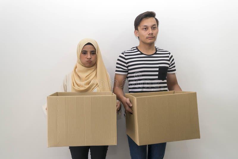 拿着房子移动的年轻马来的夫妇一个箱子 库存图片