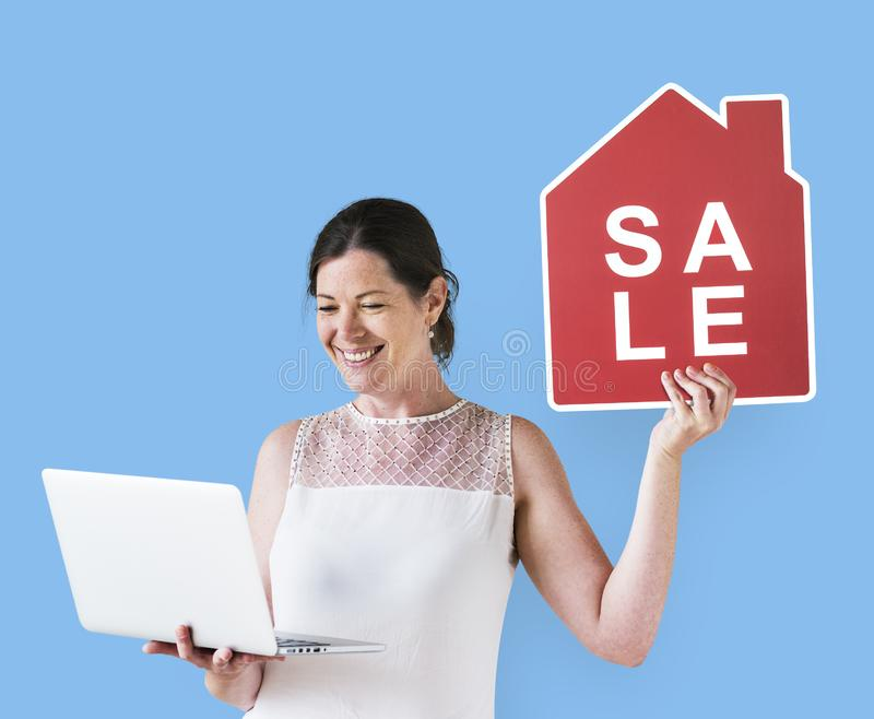 拿着房子销售象和使用膝上型计算机的妇女 免版税库存照片
