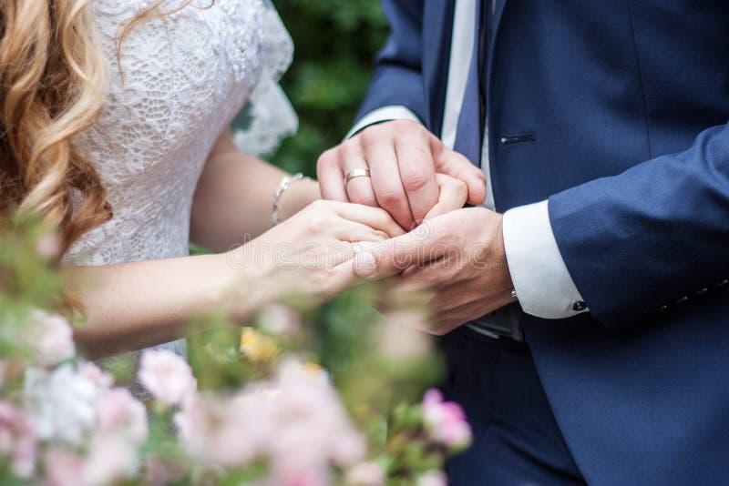 拿着手、愉快的新郎和新娘的婚姻的夫妇 爱和婚姻的概念 免版税库存照片