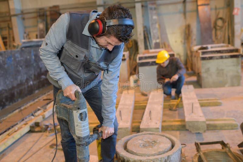 拿着手提凿岩机和打破钢筋混凝土的建筑工人 库存图片