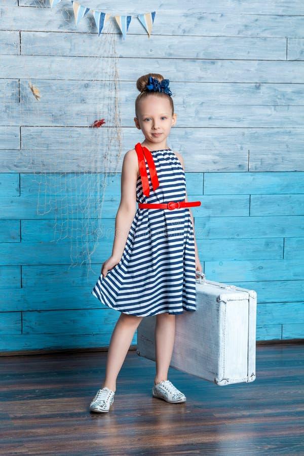 拿着手提箱的一件镶边礼服的女孩 免版税库存照片