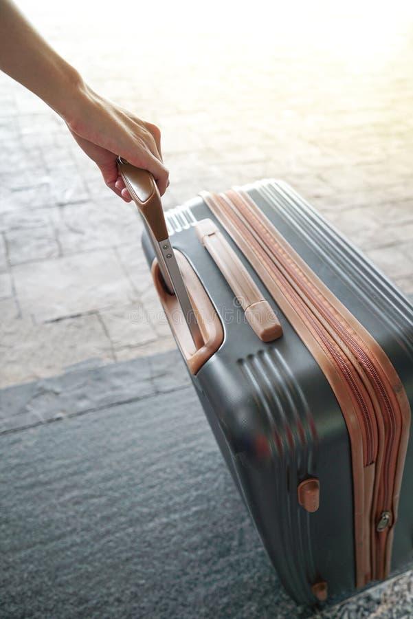 拿着手提箱的手在机场 有手提行李的妇女在机场 库存图片