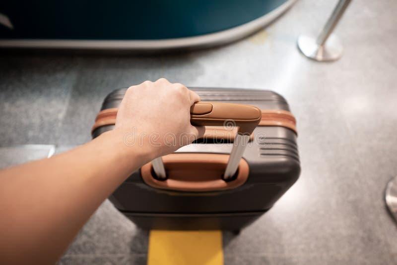 拿着手提箱的旅客手在机场 库存照片