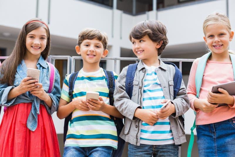 拿着手机和数字式片剂的孩子站立在学校大阳台 库存图片