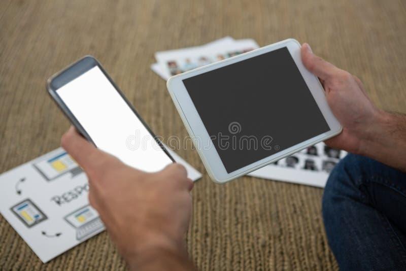 拿着手机和数字式片剂的设计师的Crpped手 图库摄影
