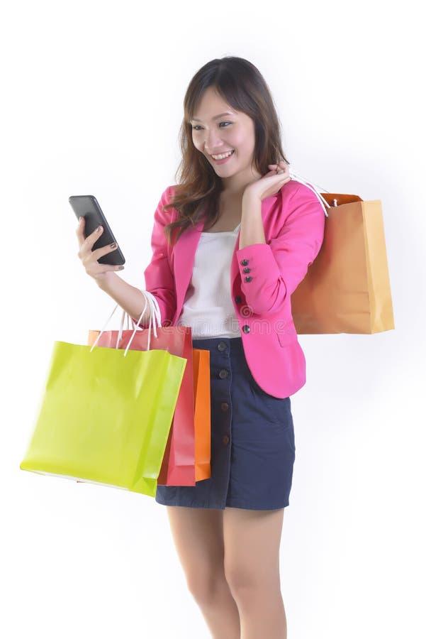 拿着手机和购物袋在白色演播室backgroundSale和购物网上概念的购物的年轻亚裔妇女 免版税库存图片