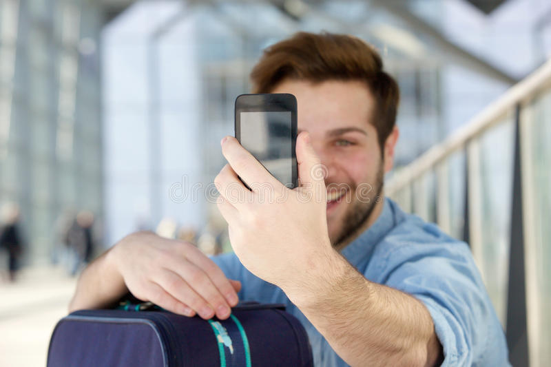 拿着手机和采取selfie的年轻人 免版税库存照片