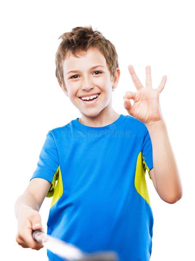 拿着手机或智能手机selfie棍子的英俊的微笑的儿童男孩拍画象照片 免版税库存照片
