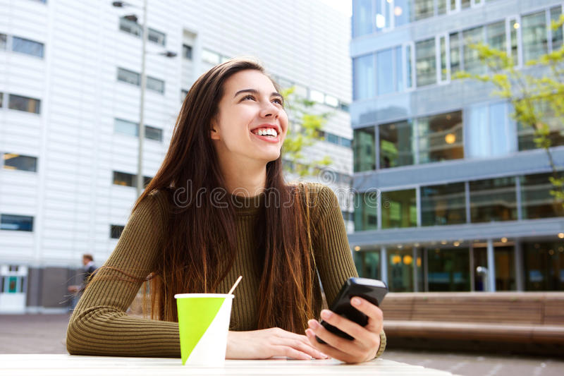 拿着手机用咖啡的微笑的少妇 免版税库存照片