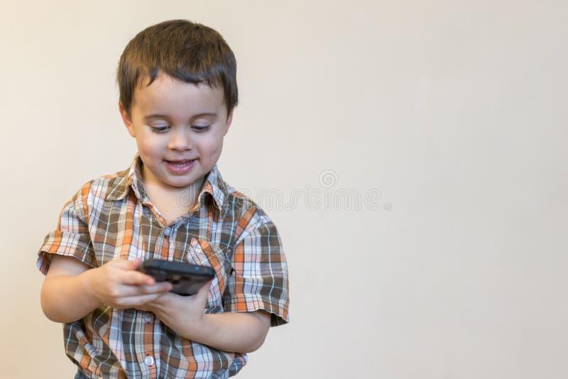 拿着手机的一个微笑的小男孩的画象被隔绝在轻的背景 打在智能手机的逗人喜爱的孩子比赛 ?? 库存图片