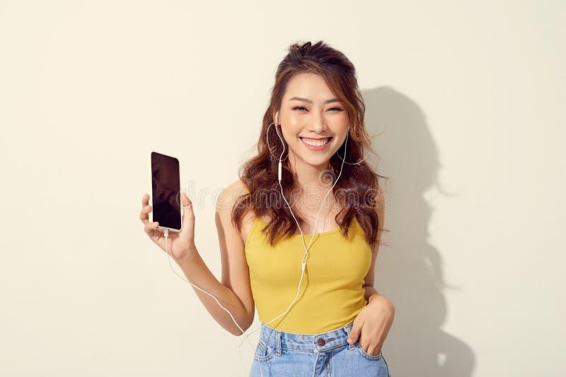 拿着手机的一快乐的美女的画象被隔绝在白色背景 库存图片
